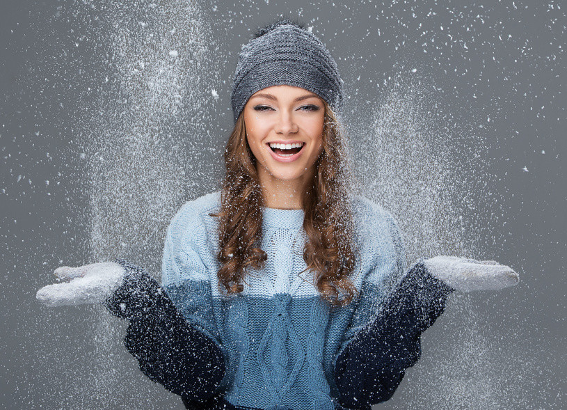 Cute girl in winter clothing with snowflakes